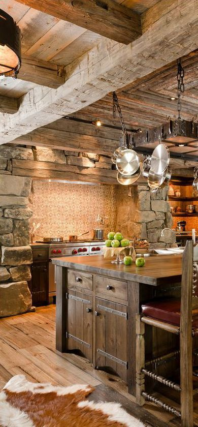 a vintage chalet kitchen with a tile backsplash, stone walls, a wooden ceiling and a large stained kitchen island