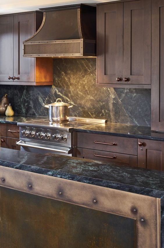 a vintage chalet kitchen with dark stained cabinets, black stone countertops, a vintage metal hood and lights