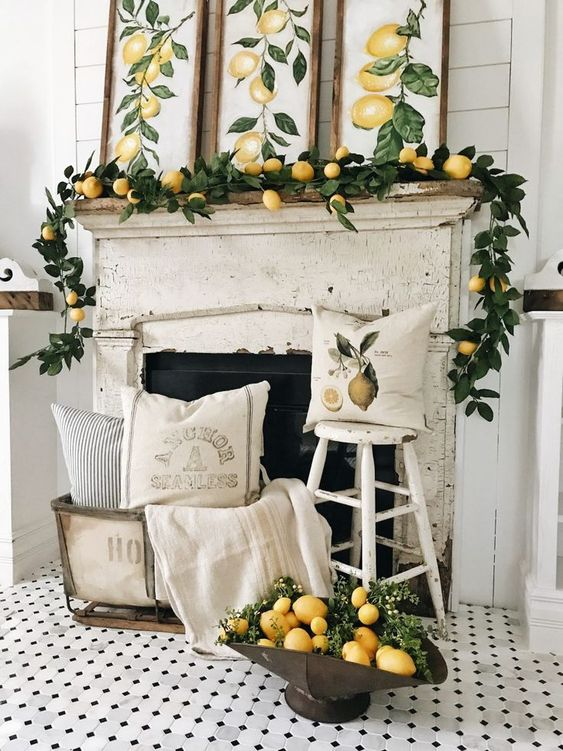 a vintage citrus inspired summer mantel with a greenery and lemon garland, lemon artworks and arrangement next to the fireplace