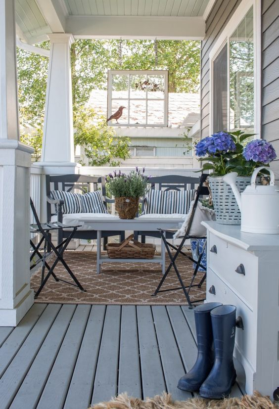 a vintage farmhouse summer porch with dark staiend furniture, striped pillows, rubber boots, a dresser and blooms