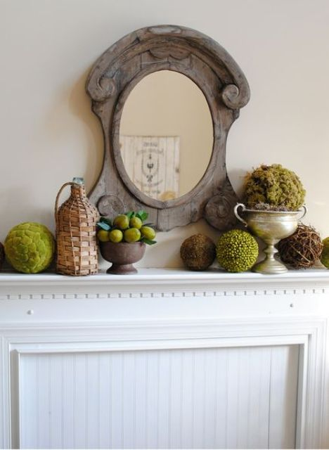 a vintage rustic mantel with a wooden mirror, moss and greenery balls, lemons and a bottle