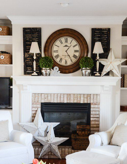 a vintage summer mantel with dark shutters, white lamps, a clock, potted greenery and large wooden stars