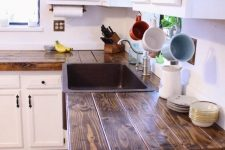 a vintage white kitchen with rich stained wooden countertops and black handles is a stylish space with a contrast
