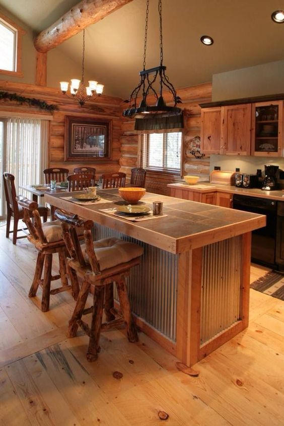 a warm and welcoming chalet kitchen clad with wood, witha  corrugated steel kitchen island and vintage lamps
