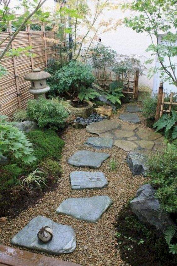 a welcomign Japanese courtyard with rocks, greenery, moss, a stone lantern and a bamboo fountain plus a low fence