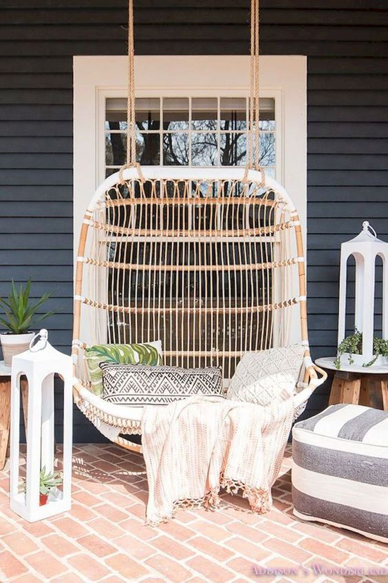 a welcoming summer porch with a large rattan hanging loveseat, an ottoman, large lanterns and potted greenery