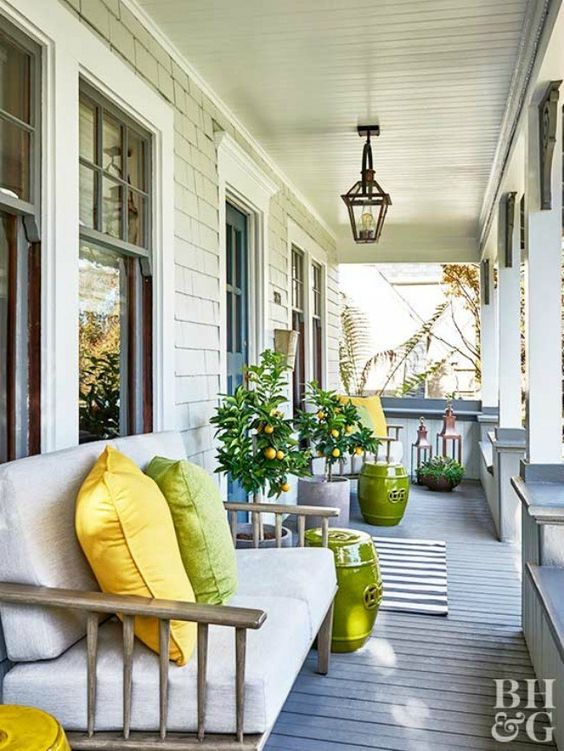 a welcoming summer porch with rattan sofas, large lanterns, green side tables and potted citrus trees