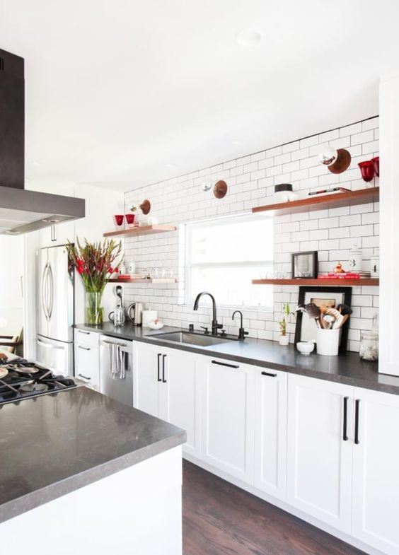 a white farmhouse kitchen with concrete countertops, black handles and appliances is very cool