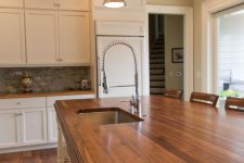 a white farmhouse kitchen with rich stained wooden countertops that add warmth and chic to the space