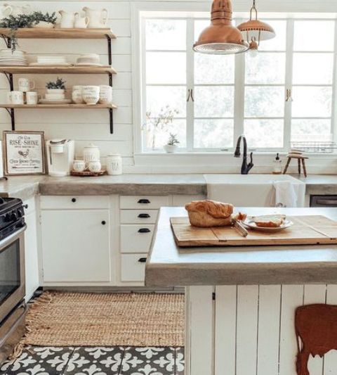 a white farmhouse kitchen with simple cabinets, concrete countertops and touches of copper for a warm look