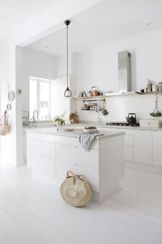 a white minimalist kitchen with sleek cabinets, concrete countertops, stainless steel appliances