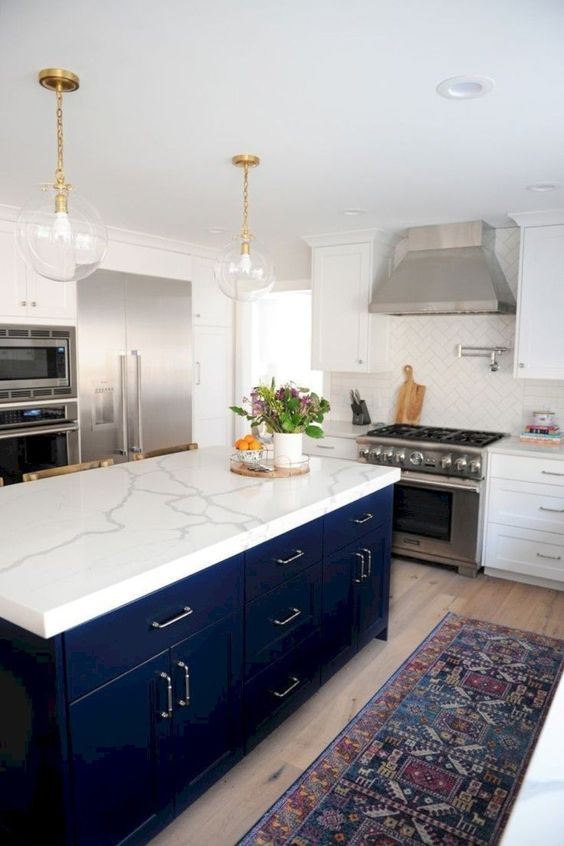a white stone countertop contrasts the navy kitchen island and makes it stand out a lot