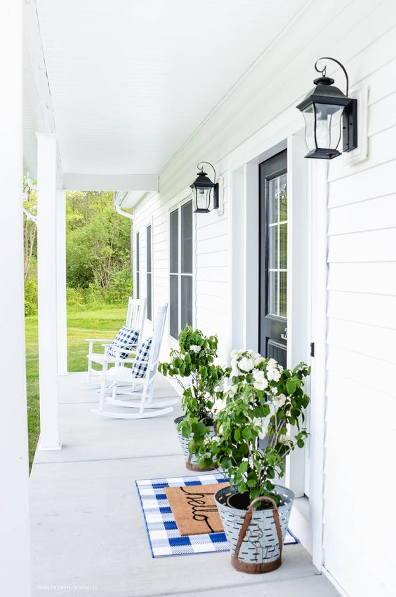 a white summer porch with comfy rocking chairs, potted greenery and blooms, a checked rug and lanterns