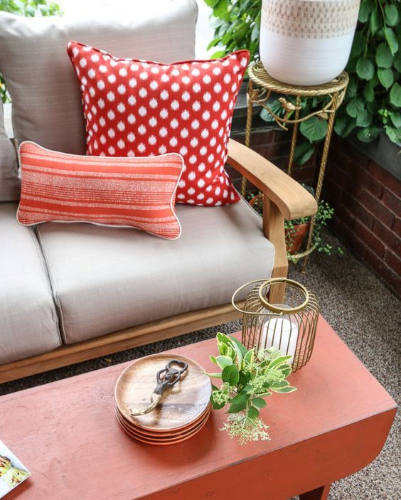 a wooden sofa, a red wooden coffee table, candle lanterns and greenery in pots