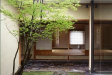 a zen indoor courtyard with some grass, rocks and a single tree growing up to the skylight for a traditional Japanese home