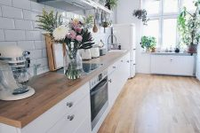 an airy Scandinavian kitchen with white cabinets and light stained wooden countertops that echo with the floors
