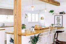 an airy modern white kitchen with light stained butcherblock countertops that match the wooden beam and pillar