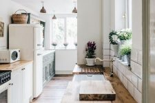 an airy white kitchen with rich stained wooden countertops and brass and darkened metal touches for a more vintage feel