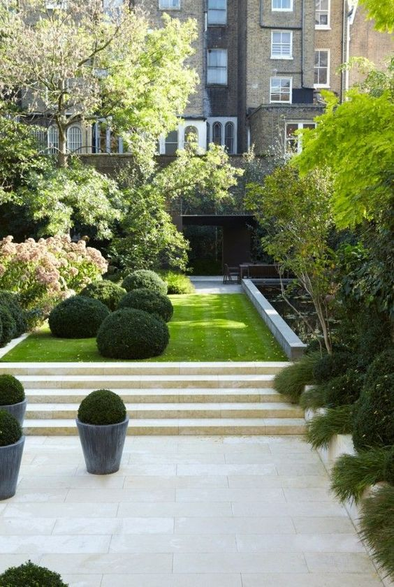 an elegant minimalist townhouse garden with stone tiles and steps, a lawn, boxwood, trees and shrubs plus a flower bed