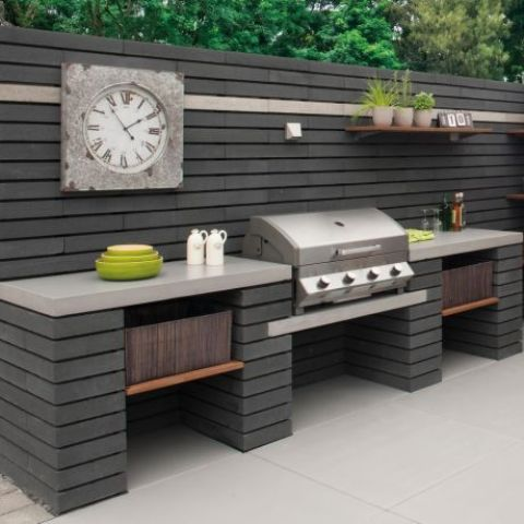 an elegant outdoor bbq area of module concrete blocks, with a large cooking space and a grill plus a clock