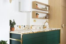 an emerald cabinet with gold touches and a colorful terrazzo countertop looks very chic and catchy