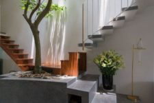 an indoor courtyard and an entryway in one, with a real tree growing in a cinder block pot and skylights over the space