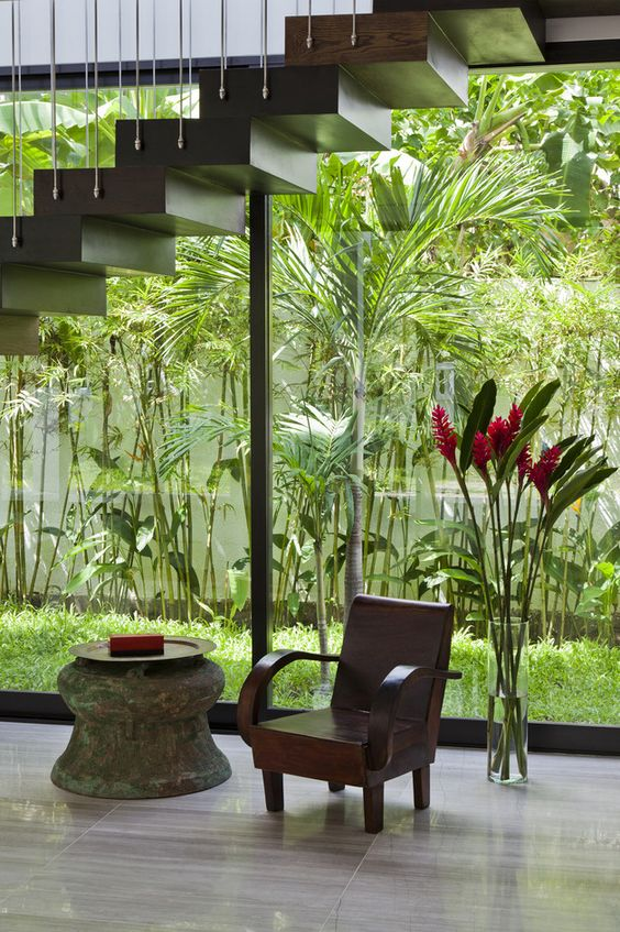 an indoor courtyard enclosed in glass, with lots of greenery and grass growing is a cool idea to refresh the spaces