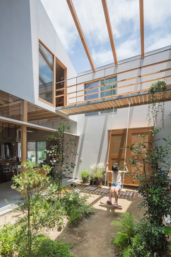 an indoor courtyard with lots of greenery growing and a glass ceiling that enlights the whole space
