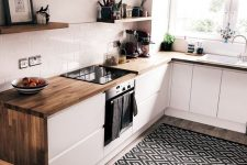 an ultra-modern white kitchen with butcherblock countertops and a printed rug looks bold and cool