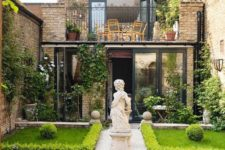 an unusual townhouse garden inspired by classics, with manicured lawns lined up with greenery, mosaic tiles and a large statue in the center