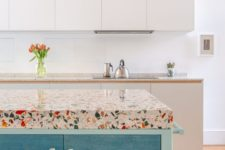 colorful terrazzo countertops spruce up the neutral kitchen and add catchiness to the bold blue island
