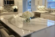 elegant neutral stone countertops complement the white kitchen and make it bolder and more eye-catching