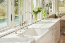 elegant white vintage-inspired cabinets plus white stone countertops that add chic to the kitchen