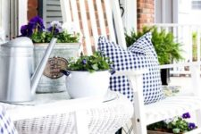 farmhouse porch decor with white wooden and wicker furniture, gingham textiles, potted blooms and greenery