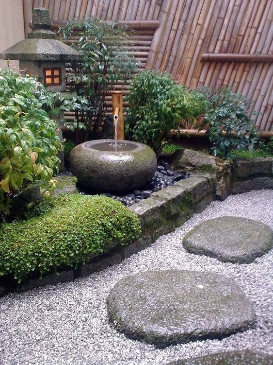 pebbles, rocks, grass, shrubs, a stone bowl fountain and a stone lantern for a lovely and chic Japanese front yard