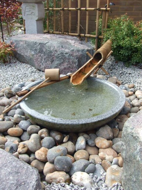 rocks, pebbles, a stone bath and bamboo fountain, greenery and mini trees for a Japanese feel in your space