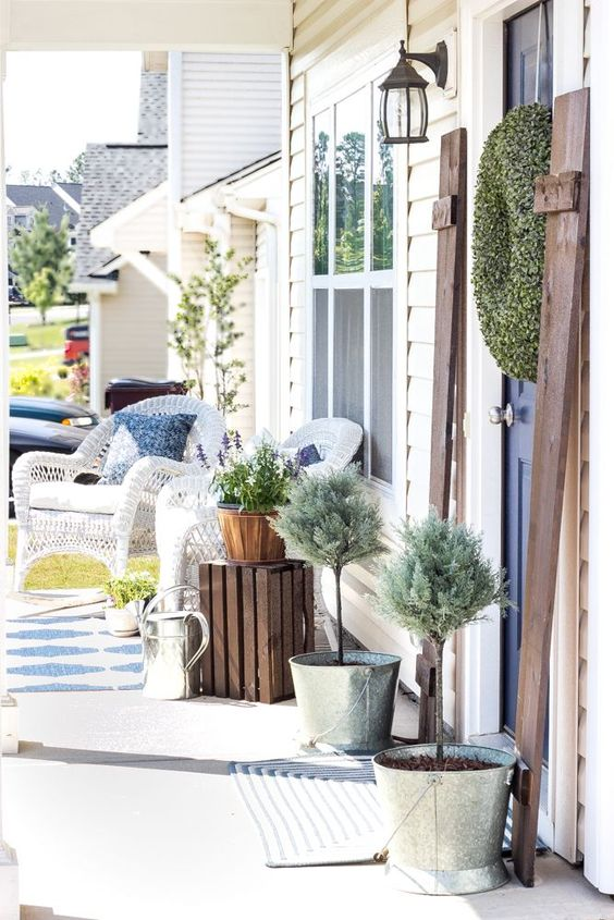 simple porch decor with white wicker chairs, potted greenery and a crate as a side table