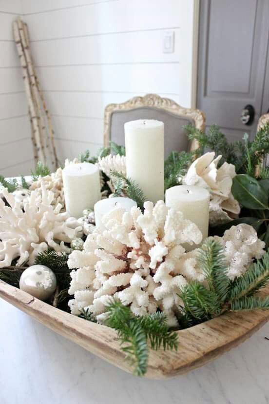 a Christmas centerpiece of a bread bowl, evergreens, corals, ornaments, candles and greenery is a lovely idea for a coastal space