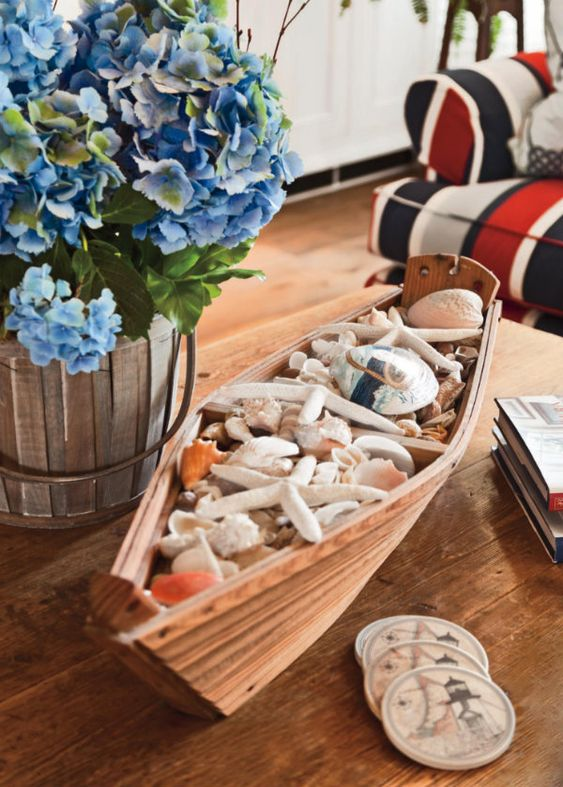 a boat filled with seashells and starfish is a nice decoration for any seaside space