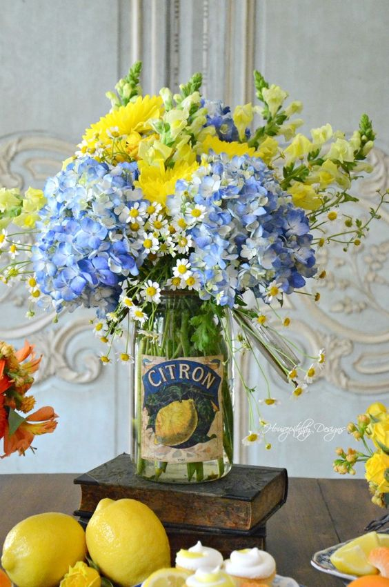 a clear jar with bright yellow and blue flowers is a bold and cool summer centerpiece with a vintage feel
