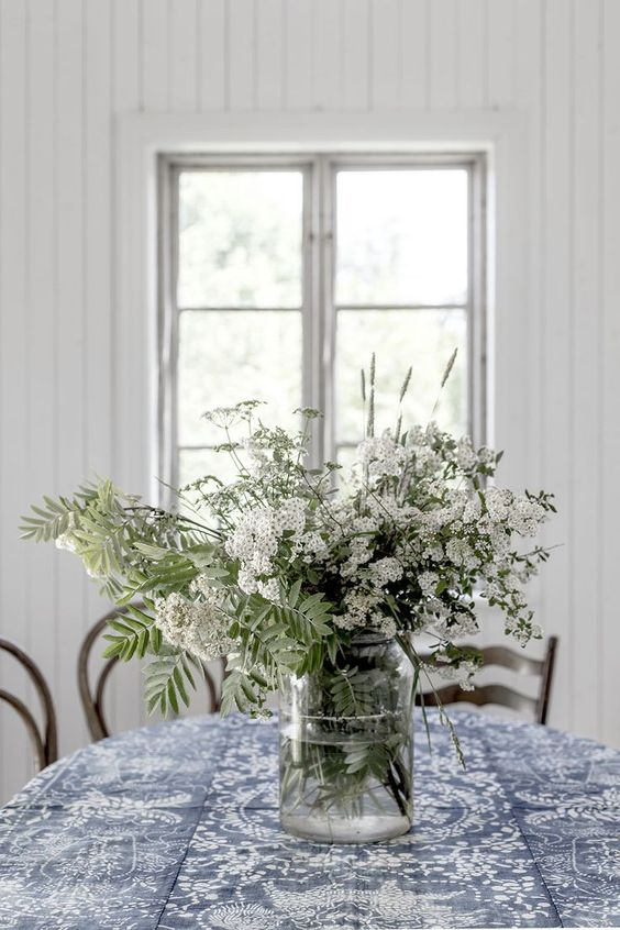 a clear vase with fresh white blooms and some leaves is a nice summer centerpiece or decoration
