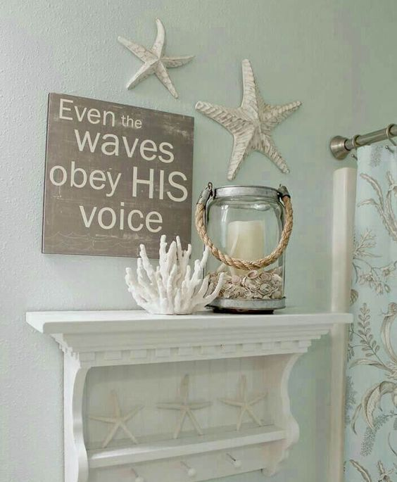 a coastal bathroom with starfish, corals and a candle lantern and with a shelf with starfish feels very cool and very stylish