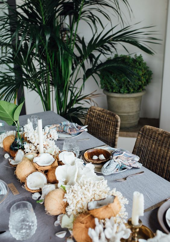 a coastal dinner tablescape with coconuts, corals and leaves plus candles is a very cool idea for a tropical space