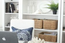 a coastal home office with a coral artwork and a coral on a stand plus greenery in pots is a very cool idea for a beachy space
