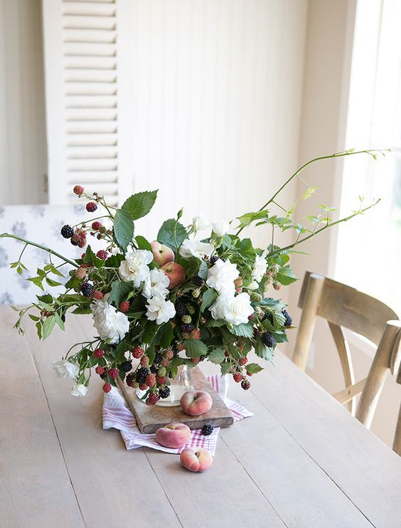 a fresh summer centerpiece or arrangement with white blooms, peaches and berries is a beautiful idea