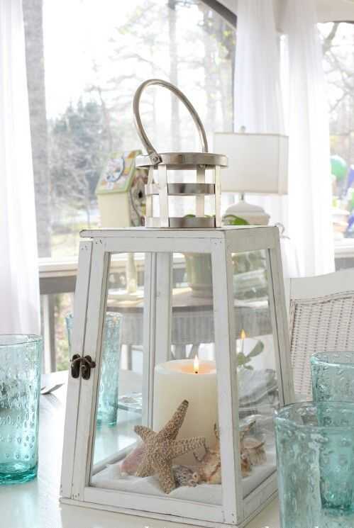 a large candle lantern with beach sand, starfish and seashells plus a large candle to decorate indoors or outdoors