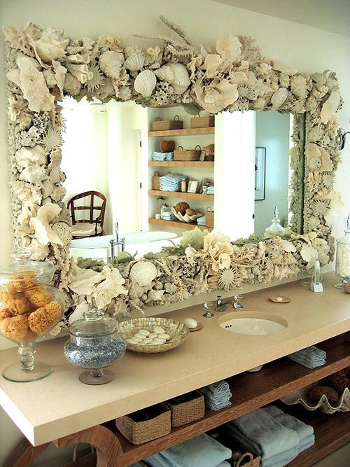 a large mirror fully clad with seashells, corals and sea urchins is a cool idea for a coastal or beach bathroom