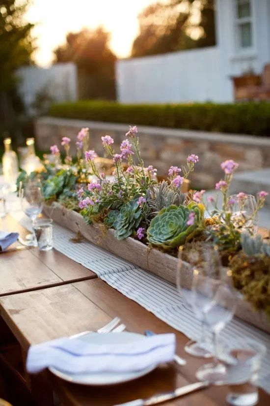 a long wooden planter with lots of succulents and some pink blooms is a chic and bold rustic centerpiece to rock