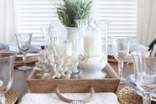 a lovely coastal farmhouse wedding centerpiece of a wooden tray, corals, candles in glasses with sand and some lavender is cool