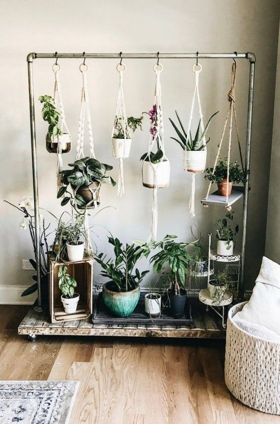 a metal and wood stand with lots of hanging planters with flowers and succulents is a very stylish idea